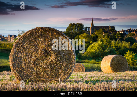 Straw Bales lie in a Wiltshire field, awaiting collection after the harvest, with Malmesbury Abbey in the background. - Stock Photo