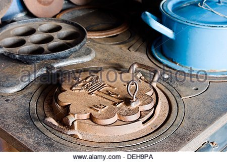 Historical coal stove with ox-eye pan, waffle iron and enamel pot in Denmark - Stock Photo