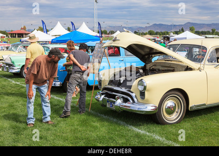 Spectators at a Classic Car show near Grand Junction, Colorado looking at a customised Oldsmobile automobile. USA - Stock Photo