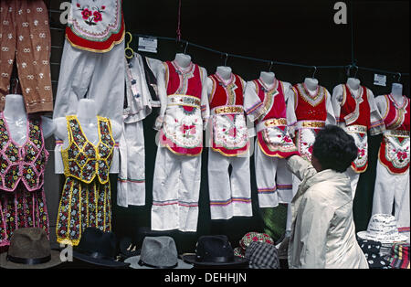 Chinese woman check clothes of Bai Minoritiy. Lijiang. Yunnan Province. China - Stock Photo