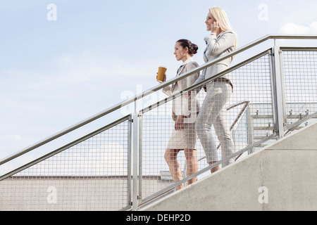 Profile shot businesswomen moving down stairs against sky - Stock Photo