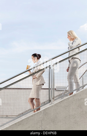 Profile shot businesswomen moving down stairs together against sky - Stock Photo
