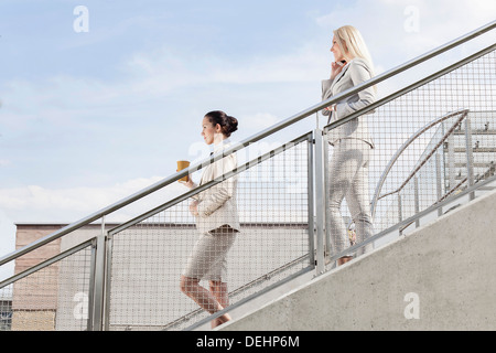 Profile shot businesswomen holding disposable cup mobile phone while moving down stairs together against sky - Stock Photo