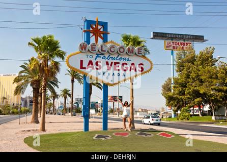 Young woman posing beside 'Welcome to Fabulous Las Vegas' sign on Las Vegas Boulevard South. JMH5454 - Stock Photo
