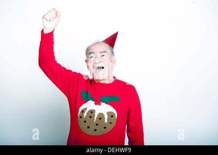 Senior adult man wearing Christmas jumper raising his arm the air - Stock Photo