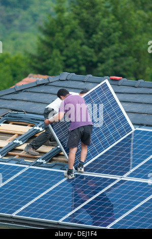 Installation of photovoltaic solar panels on roof of house, Germany - Stock Photo