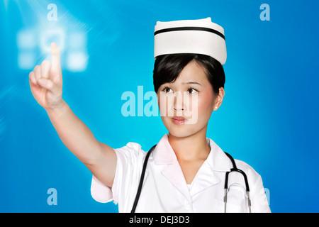 Female nurse using futuristic touch screen over blue background - Stock Photo