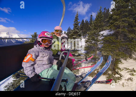 Children and their mother ride the chairlift at Lake Louise Mountain Resort, Lake Louise, Banff National Park, Alberta, - Stock Photo