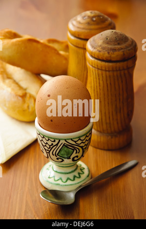 breakfast egg with salt, pepper and bread on a wooden background - Stock Photo