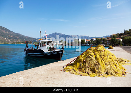 Fishing nets drying on harbour harbor wall in front of boat Nidri Lefkas Lefkada Greek Island Greece typical scene - Stock Photo