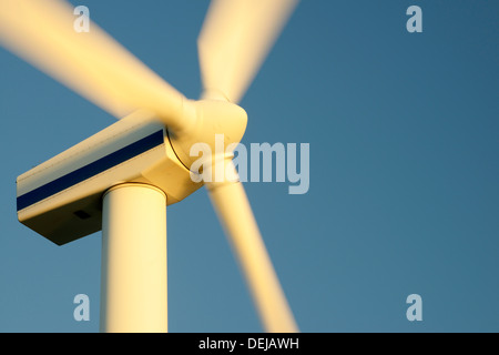 Wind turbine rotors with blue sky generating electricity on wind farm at Workington, Cumbria, England, UK. Warm - Stock Photo