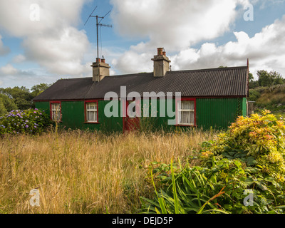 an old derelict house with overgrown weeds - Stock Photo