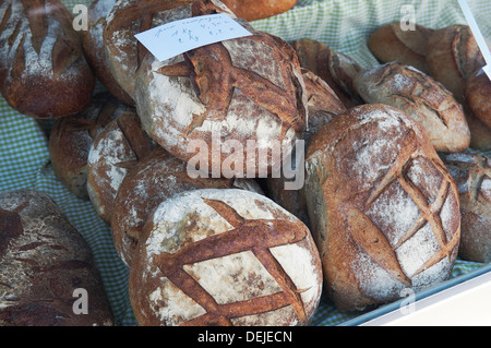rustic french artisan bread on food market stall, normandy, france - Stock Photo