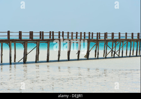 Long wooden jetty on a tropical island stretching out into the sea over a lagoon - Stock Photo