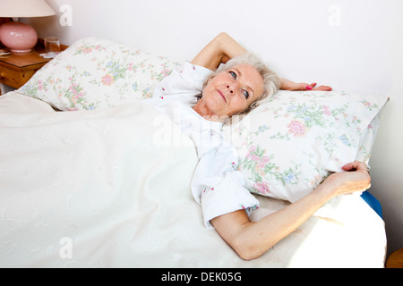 High angle view senior woman looking away while lying bed home - Stock Photo