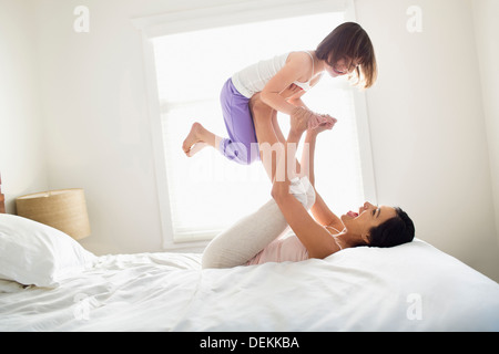 Mother and daughter playing on bed - Stock Photo