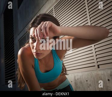 Caucasian runner wiping sweat off forehead