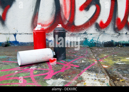 Spray paint cans by graffiti wall - Stock Photo