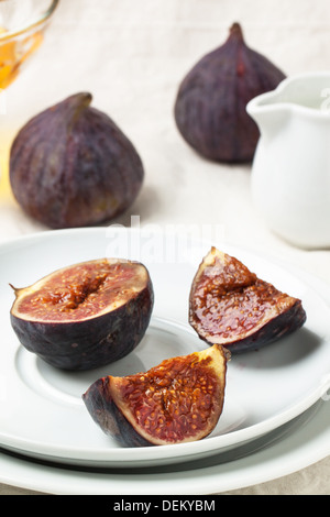 White plate with sliced figs served on white tablecloth - Stock Photo