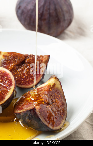 White plate with sliced figs and flowing honey - Stock Photo
