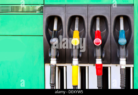 Four gas pump nozzles on the petrol station - Stock Photo