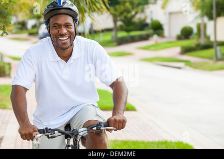 A happy African American man riding his bicycle outside wearing shorts, helmet and polo t-shirt - Stock Photo
