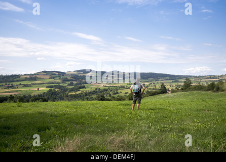 Pilgrim walker admiring the landscape on the route GR65, The Way of St James, between Le Chier and St-Privat-d'Allier, - Stock Photo