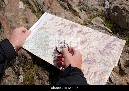 Man holding compass and map of the Lake District Cumbria England UK United Kingdom GB Great Britain - Stock Photo