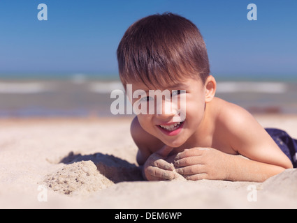 Portrait of a cute happy child playing in the sand on the beach. Lake Huron, Ontario, Canada. - Stock Photo