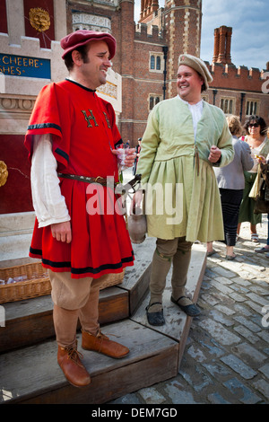 Actors in period costume hand out glasses of wine at the Henry VIII wine fountain in Base Court at Hampton Court - Stock Photo