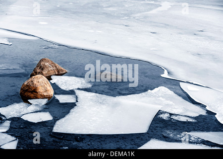 Broken ice floating on water at cold lake shore with rocks in winter - Stock Photo