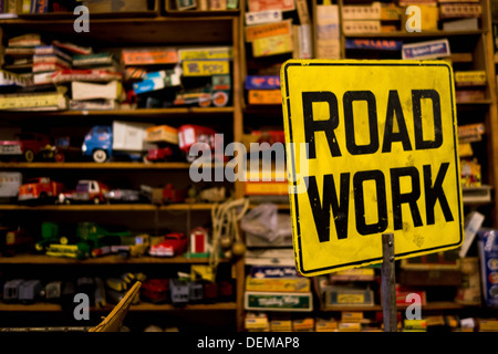 A 'road work: sign in front of vintage toys in a Pittsburgh antique shop.  Vintage toy trucks on the crowded shelves. - Stock Photo