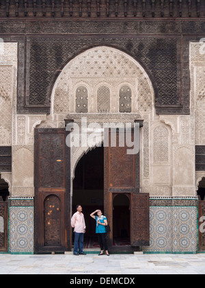 Western tourist talking to local guide at the Bou Inania madrasa in Fez, Morocco - Stock Photo