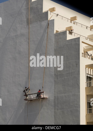 Construction workers painting outer building wall - Stock Photo