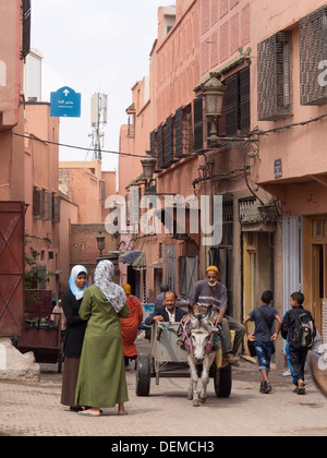Women chatting next to men riding in a cart pulled by a donkey in the streets of Marrakech, Morocco - Stock Photo