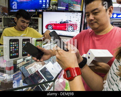 Bangkok, Thailand. 21st Sep, 2013. Men look at the iPhone 5s in an electronics shop in MBK in Bangkok. Customers - Stock Photo