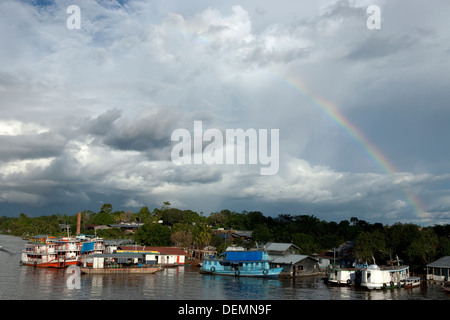 Rainbow appears on the Amazon River after a heavy storm. - Stock Photo