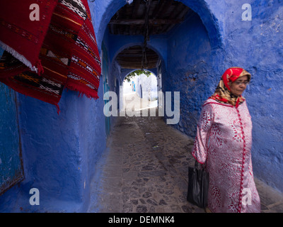 Woman walking down a street with blue painted houses in Chefchaouen, Morocco - Stock Photo