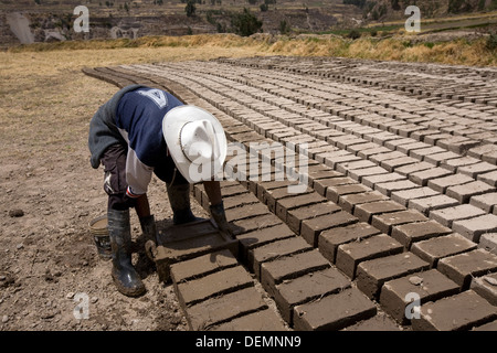 A man made ​​adobe bricks for use in construction of houses in the town of Yanque, near the source of the Amazon - Stock Photo