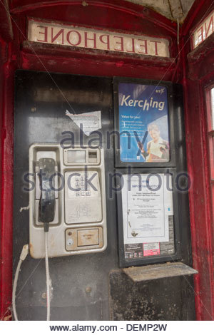 Traditional red telephone box still in use but in a state of disrepair, and now proposed to be removed by BT - Stock Photo