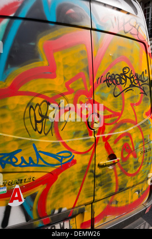 Graffiti on delivery van in Paris, France - Stock Photo