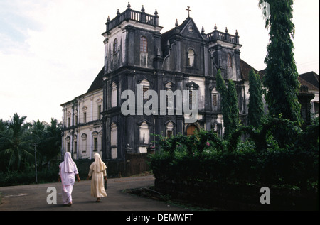 Two catholic nuns walking in front of Church and convent of St John of God in Old Goa, Panjim, India - Stock Photo