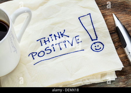 think positive - motivational slogan on a napkin with a cup of coffee - Stock Photo