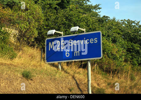 A British road sign directing traffic to the next services on the M25 motorway. - Stock Photo