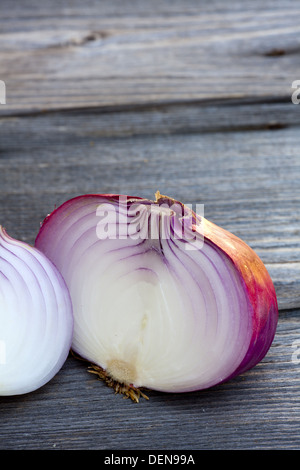 Close up view of a whole and a halved fresh red onion on a old wooden Table - Stock Photo