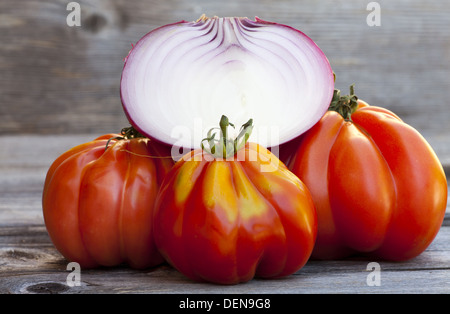 Three Oxheart Tomato and a halved red Onion from Weekly Market in South France on a old wooden Table - Stock Photo