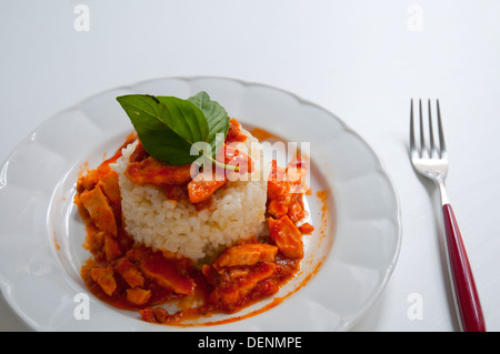 Rice with chicken and tomato sauce, with two leaves of basil. Close view. - Stock Photo