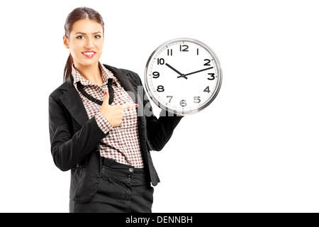 Smiling female standing and pointing on a wall clock - Stock Photo