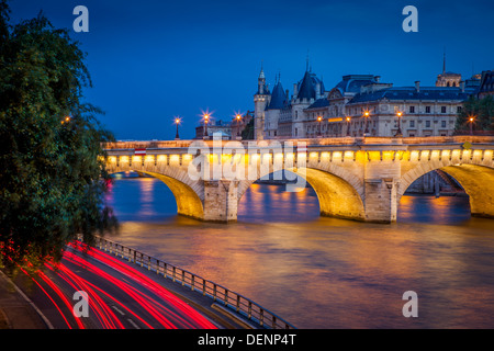 Twilight over Pont Neuf and the Conciergerie along River Seine, Paris France - Stock Photo