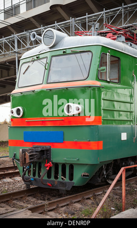 Green locomotive with red stripes on the cabin stands on the railway station - Stock Photo